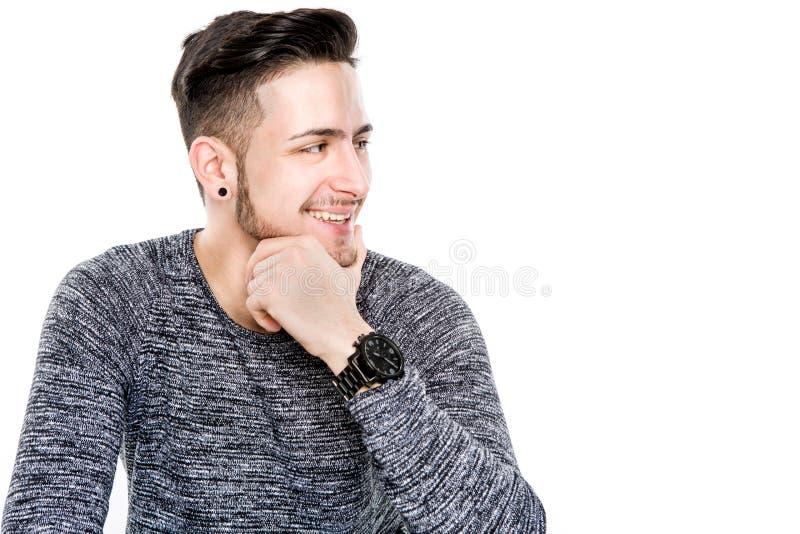 Jeune homme occasionnel posant avec le sourire de dent sur le plancher tandis que regard photographie stock libre de droits