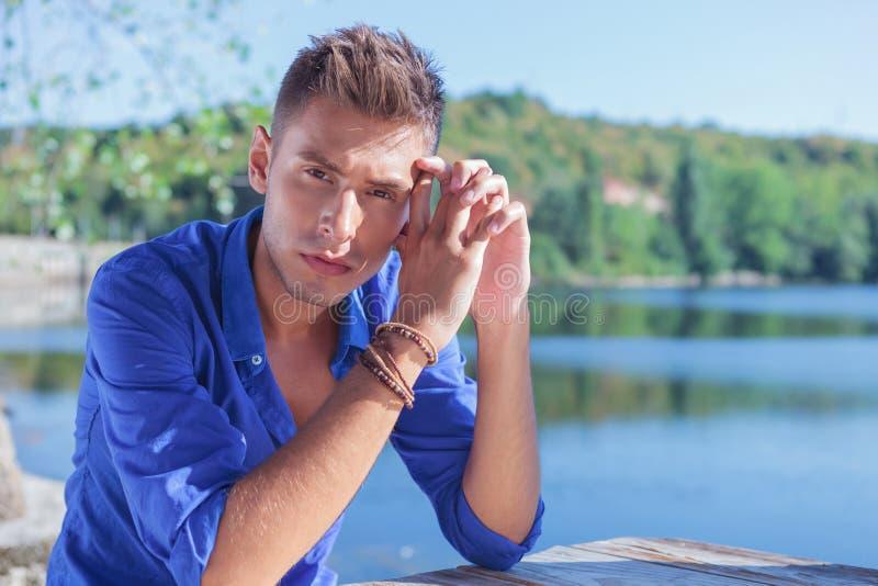 Homme posant à la table près du lac photo stock
