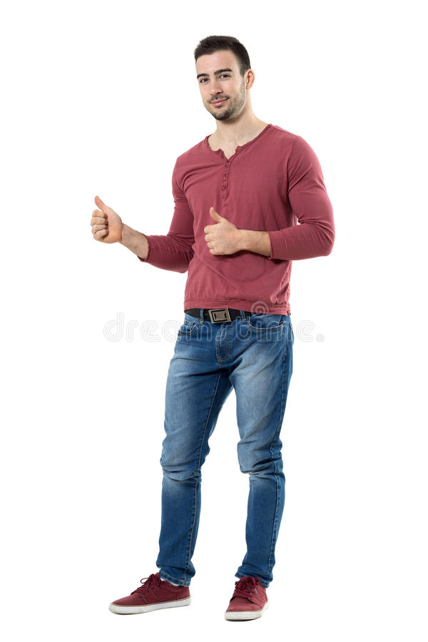 Jeune homme occasionnel réussi montrant des pouces regardant l'appareil-photo image libre de droits