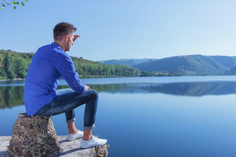 L'homme s'assied par le lac et regarde loin photo libre de droits