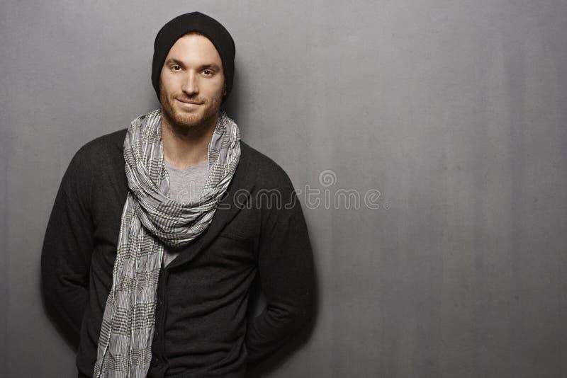 Jeune homme occasionnel souriant au-dessus du mur gris photo stock