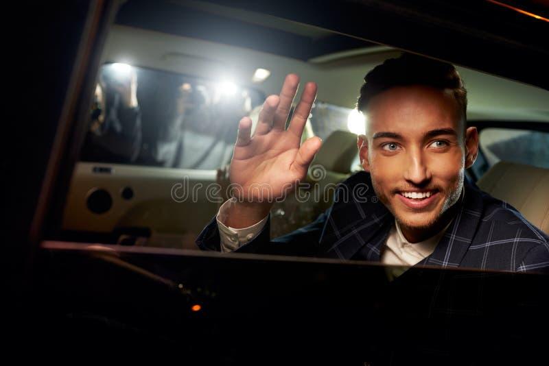 Jeune homme ondulant de derrière d'une limousine conduite par chauffeur photos stock