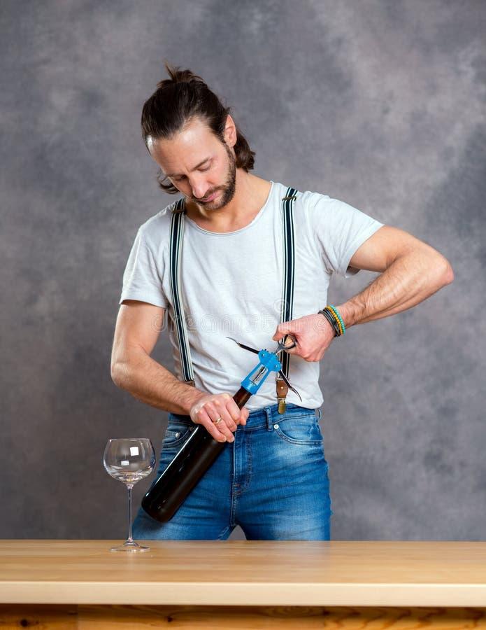 Jeune homme ouvrant le vin rouge photos stock