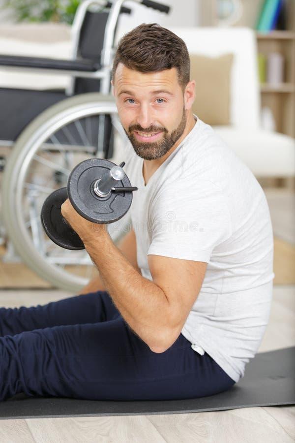 Jeune homme parapl?gique handicap? bel dans le fauteuil roulant faisant le sport de r?adaptation photo libre de droits