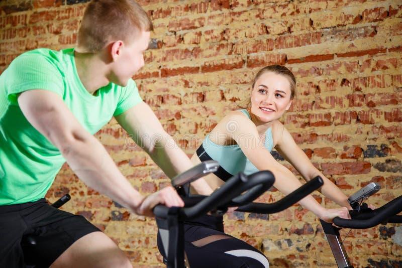 Jeune homme parlant à une blonde mignonne tandis qu'ils chacun des deux en font cardio- sur une bicyclette au gymnase Orientation photos libres de droits