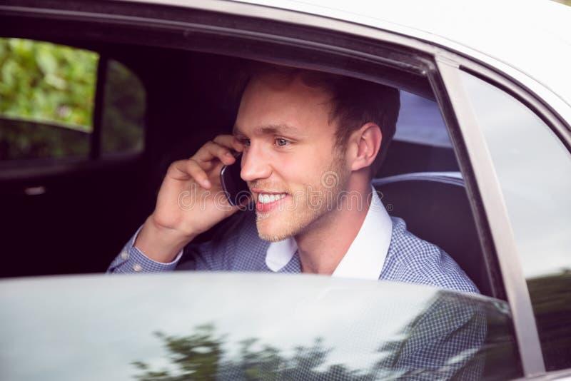 Jeune homme parlant au téléphone dans la limousine image stock
