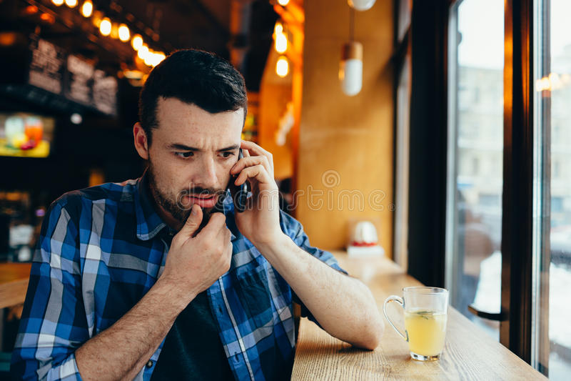 Jeune homme parlant au téléphone en café photo stock