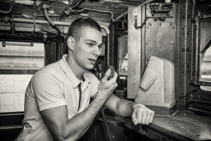 Jeune homme parlant dans la radio dans le moteur de train images stock