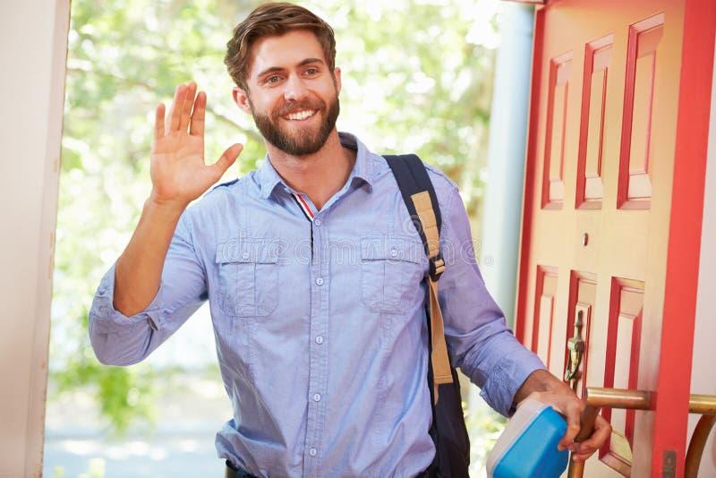 Jeune homme partant à la maison pour le travail avec le déjeuner emballé images libres de droits