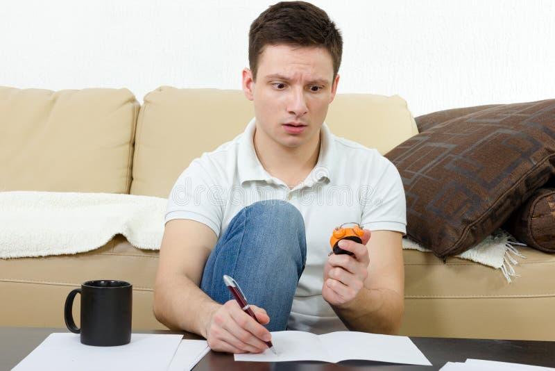Jeune homme passant l'examen et comptant des minutes tenant la montre image stock