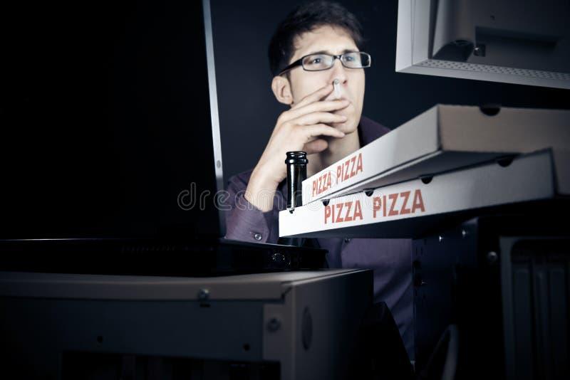 Jeune homme passant sa nuit avec des ordinateurs images libres de droits