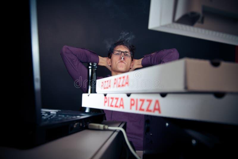 Jeune homme passant sa nuit avec des ordinateurs images stock