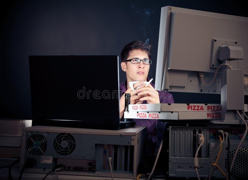 Jeune homme passant sa nuit avec des ordinateurs photo libre de droits