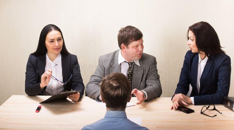 Jeune homme pendant l'entrevue d'emploi et membres de gestion image libre de droits