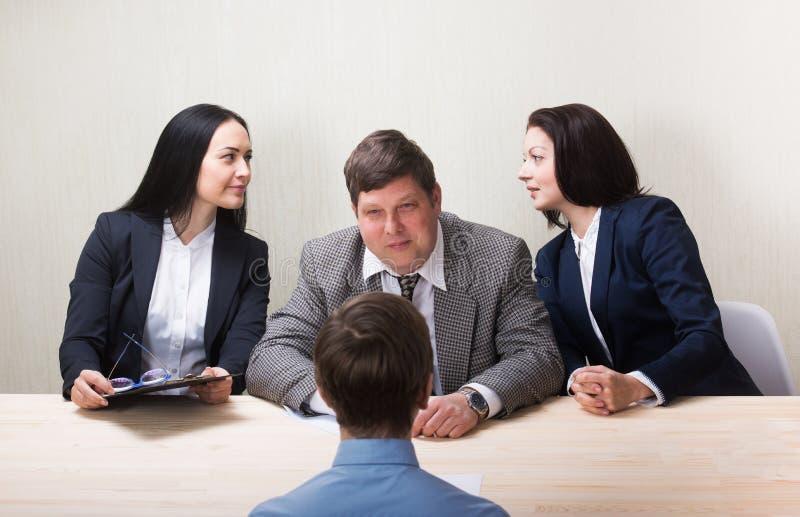 Jeune homme pendant l'entrevue d'emploi et membres des managemen photos stock