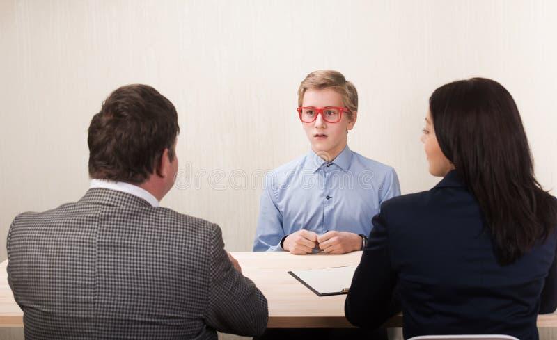 Jeune homme pendant l'entrevue d'emploi et membres des managemen photo libre de droits