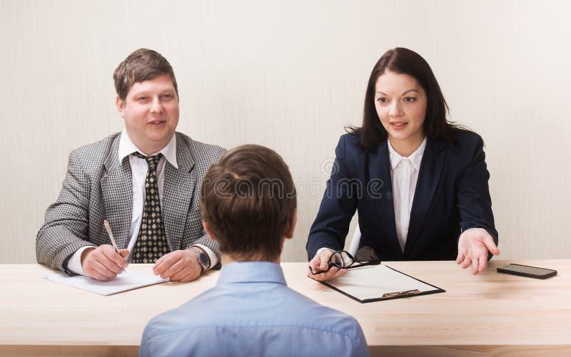 Jeune homme pendant l'entrevue d'emploi et membres des managemen images stock