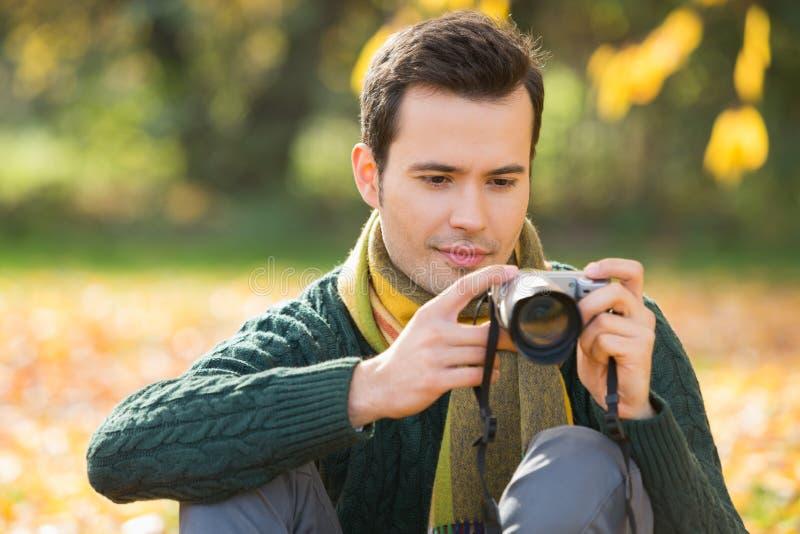 Jeune homme photographiant en parc pendant l'automne photos libres de droits