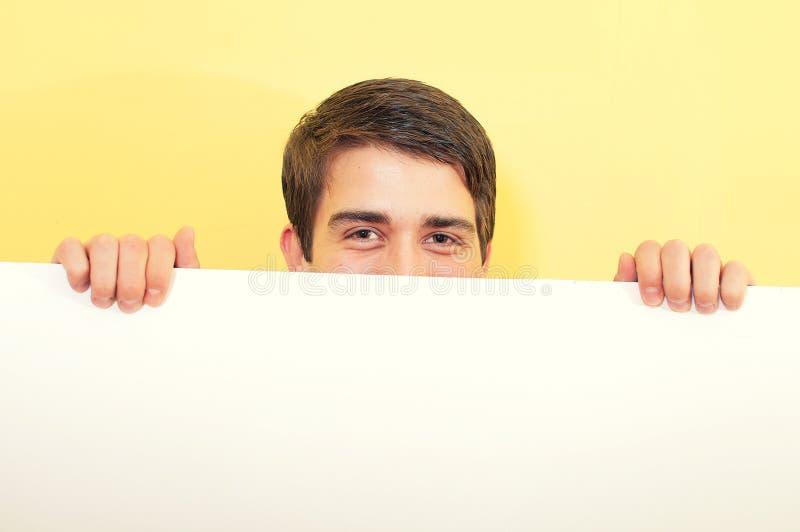Jeune homme piaulant ou regardant au-dessus d'un panneau blanc photographie stock