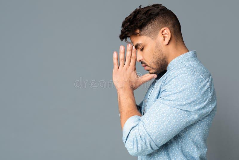 Jeune homme plein d'espoir tenant des mains dans le geste de prière Vue de c?t? photographie stock libre de droits