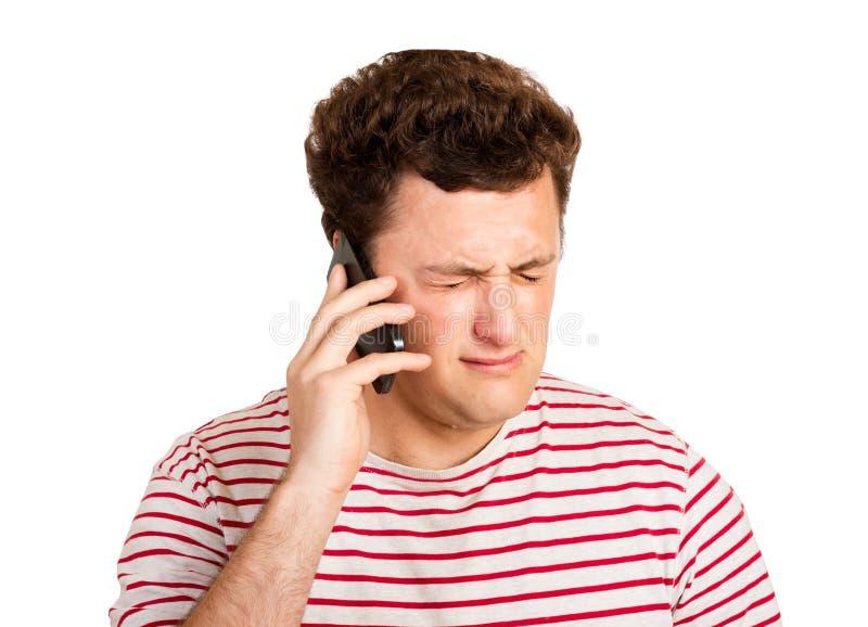 Jeune homme pleurant au-dessus de la mauvaise nouvelle qu'il reçoit à son téléphone Homme émotif d'isolement sur le fond blanc images stock