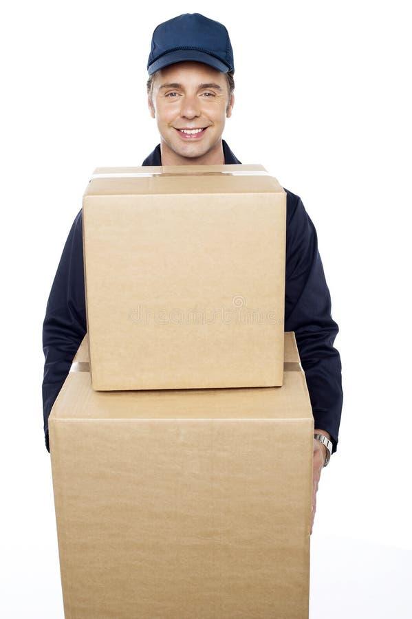 Jeune homme portant les boîtes en carton énormes image libre de droits