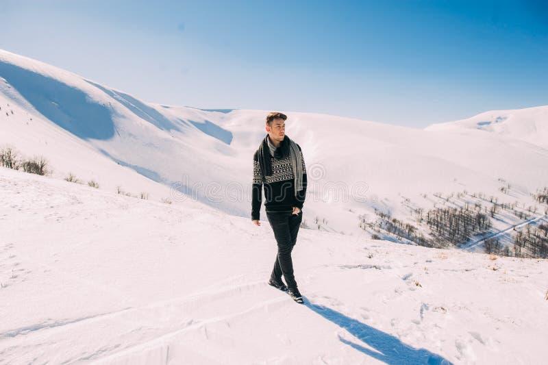 Jeune homme posant sur un fond des montagnes neigeuses photographie stock