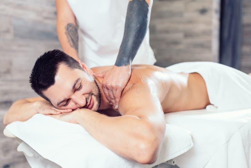Jeune homme positif appréciant obtenant le massage au centre de station thermale image libre de droits