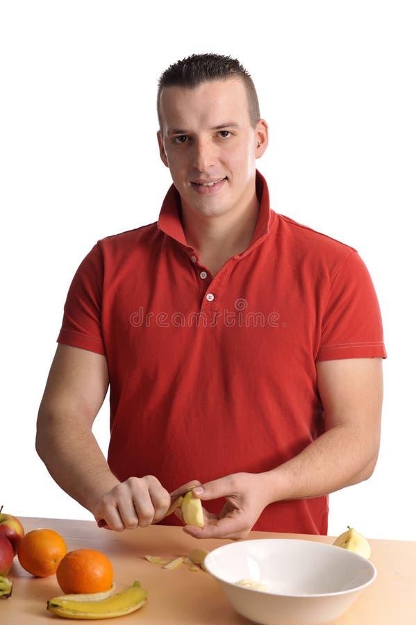 Jeune homme préparant une salade de fruits photo stock