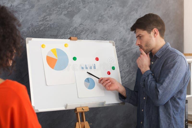 Jeune homme présentant l'exposé au collègue images stock