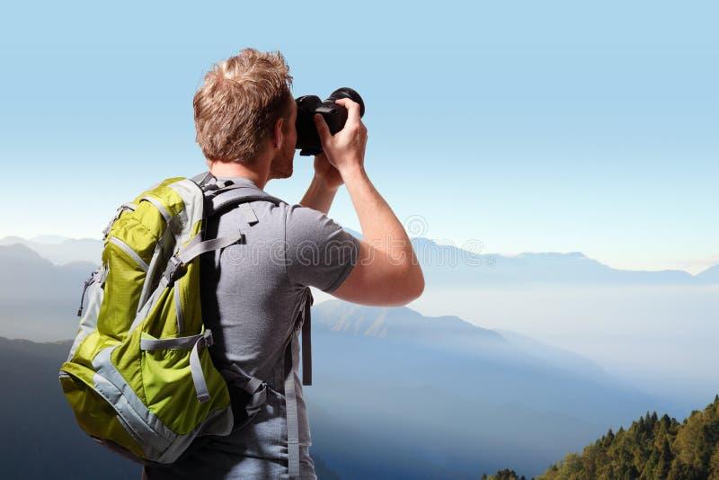 Jeune homme prenant la photo sur la montagne images stock