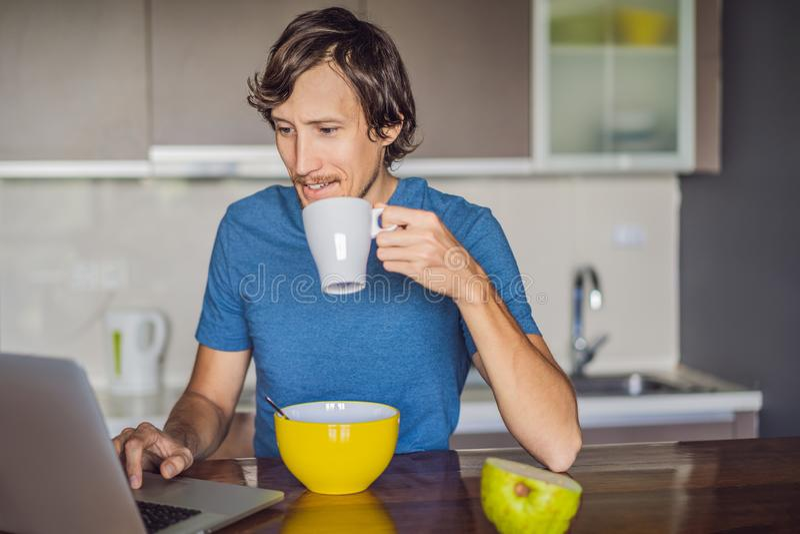 Jeune homme prenant le petit d?jeuner et ? l'aide de l'ordinateur portable sur la cuisine photographie stock libre de droits