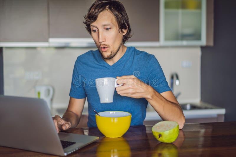 Jeune homme prenant le petit d?jeuner et ? l'aide de l'ordinateur portable sur la cuisine photos stock