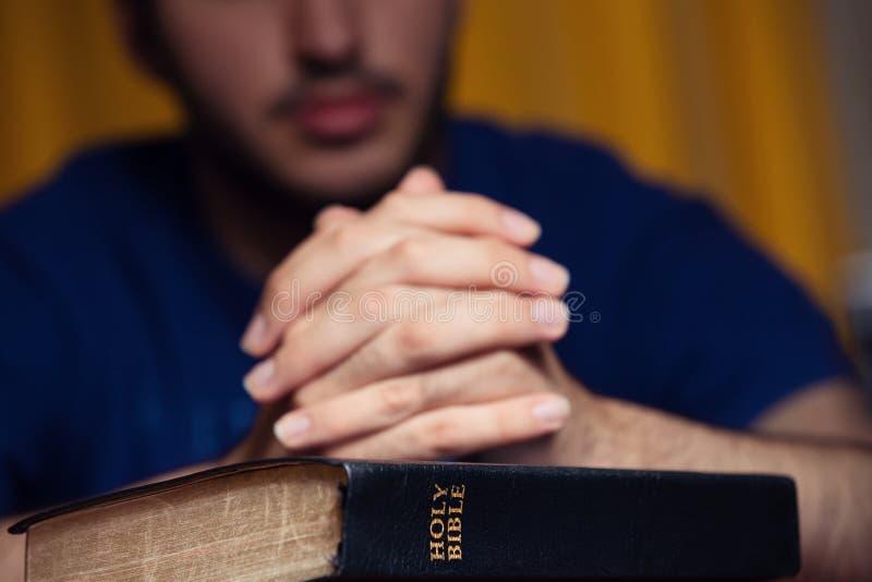 Jeune homme priant sur la bible image stock