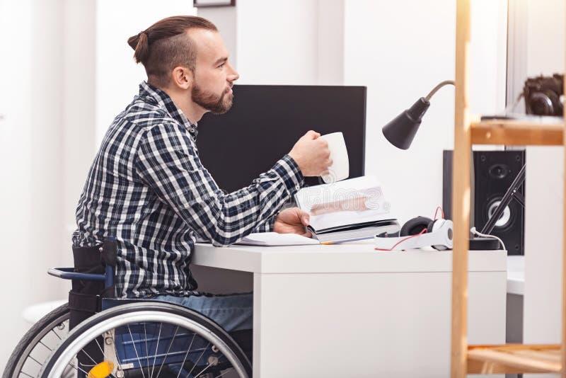 Jeune homme réfléchi s'asseyant à la table images libres de droits