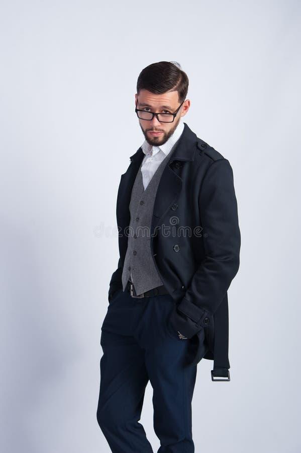 Jeune homme réussi dans un manteau noir photo libre de droits