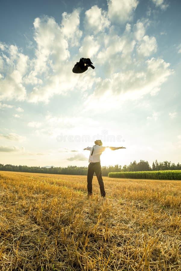 Jeune homme réussi jetant son manteau dans le ciel image stock