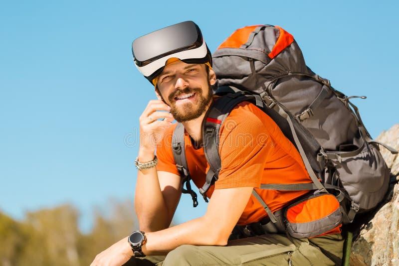 Jeune homme réussi, utilisant des lunettes de réalité virtuelle à voyager en montagnes, des vacances en été photos libres de droits