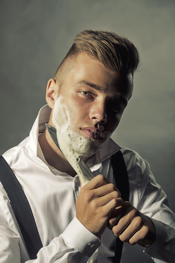 Jeune homme rasant avec le couteau photos stock