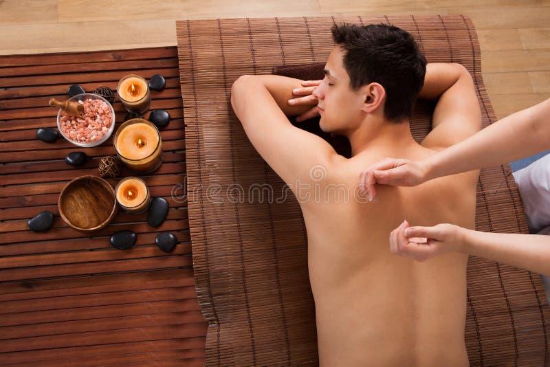 Jeune homme recevant le massage arrière dans la station thermale image libre de droits
