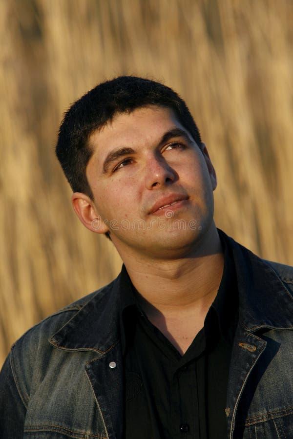 Jeune homme regardant de côté avec un regard pensif images stock