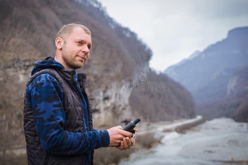 Jeune homme regardant des généralistes d'un navigateur sur la banque d'une rivière de montagne pendant un voyage extrême photo stock