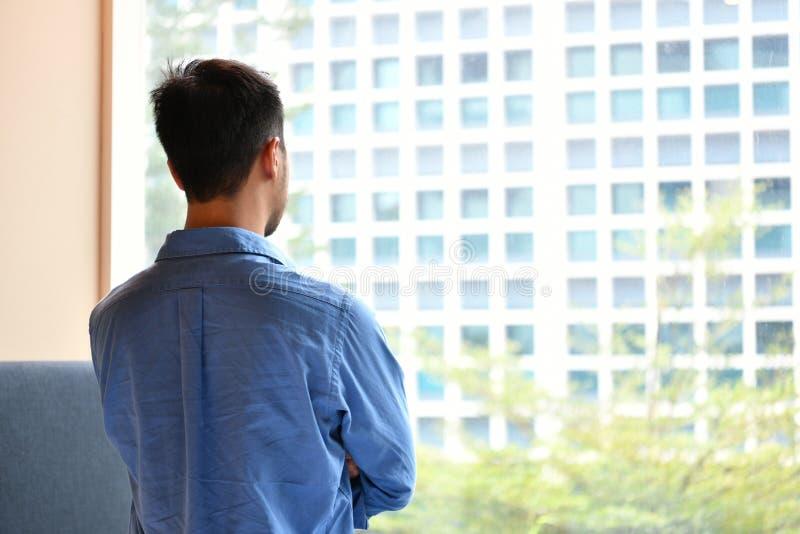 Jeune homme regardant hors de la fenêtre dans la chambre photographie stock libre de droits