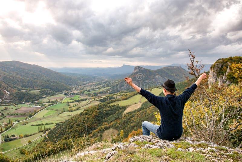 Jeune homme regardant la montagne le coucher du soleil image libre de droits
