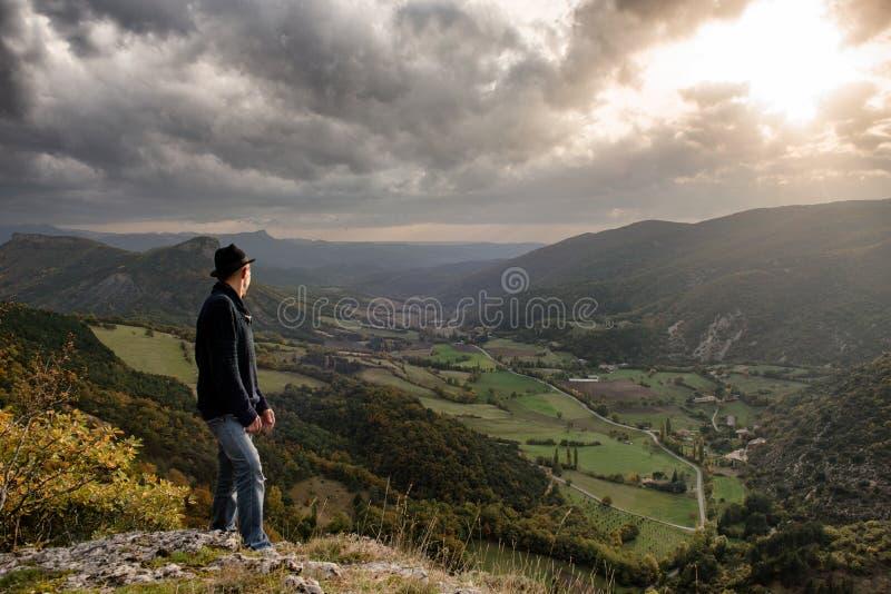 Jeune homme regardant la montagne le coucher du soleil photos stock