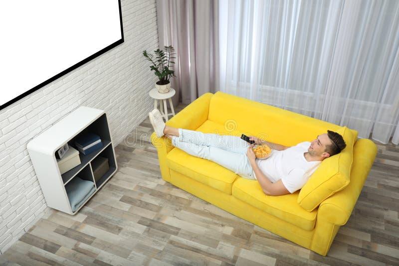 Jeune homme regardant la TV et mangeant des puces sur le sofa à la maison, au-dessus de la vue photo libre de droits