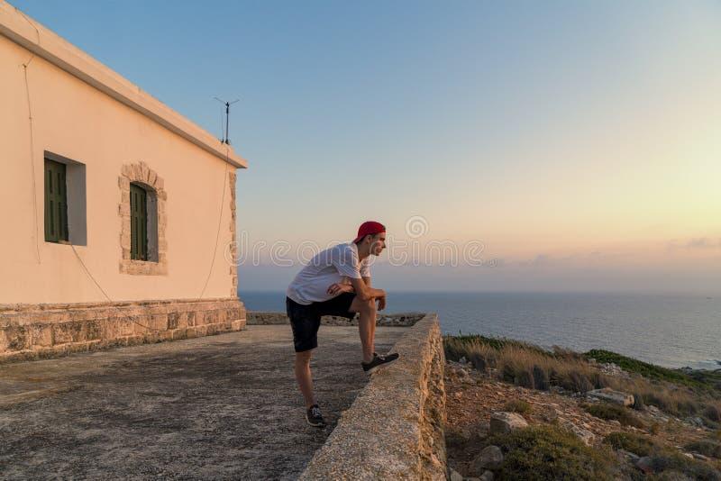 Jeune homme, regardant le coucher du soleil images stock