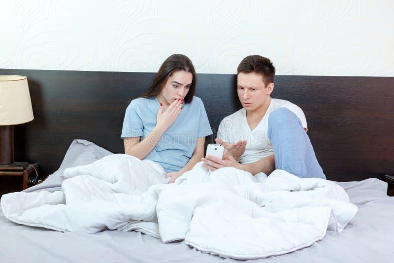 Jeune homme regardant le téléphone avec la femme choquée et étonnée à côté de images stock