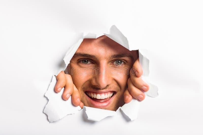 Jeune homme regardant par la déchirure de papier photo stock