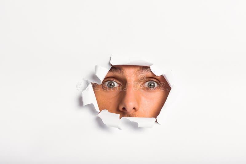 Jeune homme regardant par la déchirure de papier photos libres de droits